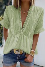 Zielona bluzka w szwajcarskie kropki z falbaną i dekoltem V