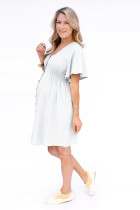 Biała sukienka ciążowa zapinana na guziki z dekoltem V