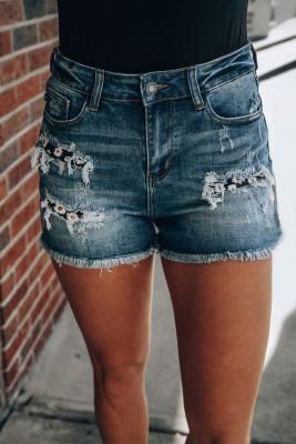 Pantalones cortos de mezclilla con parches de margaritas desgastados en azul lavado medio